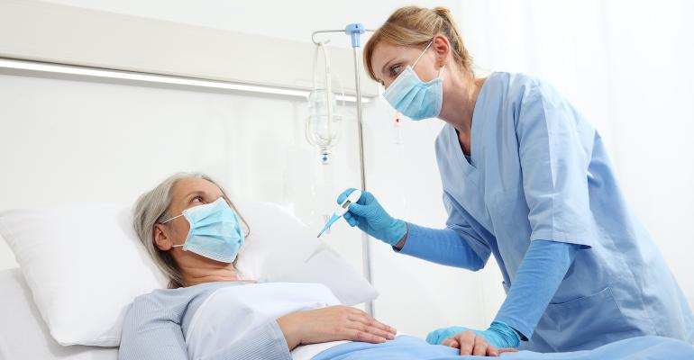 female-patient-with-mask-lying-prone-on-bed-while-treated-by-female-nurse.jpg