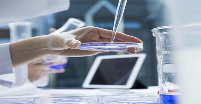lab tech dropping liquid on a petri dish