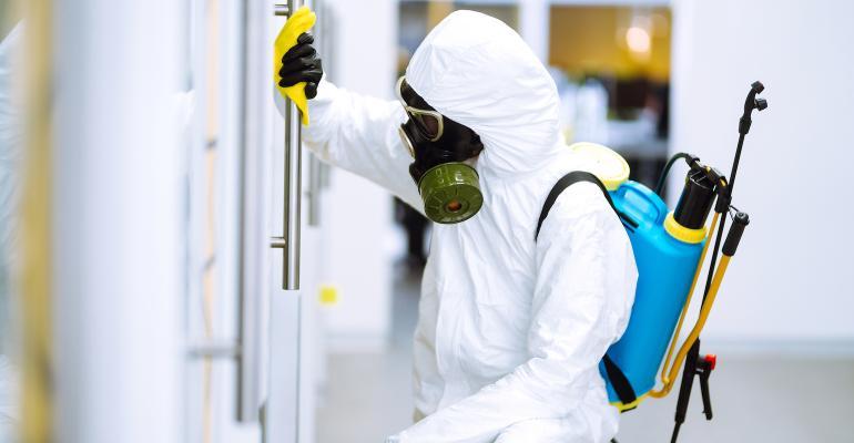person-wearing-hazmat-suit-disinfecting-a-door.jpg